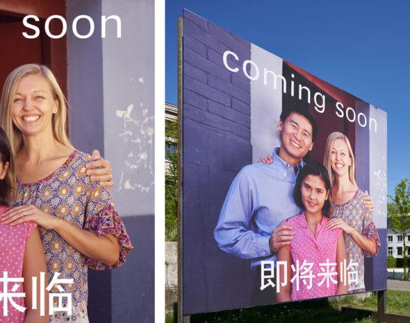 """vor dem NS-Dokumentationszentrum steht ein Billboard, auf dem eine multikulturelle Kleinfamilie zu sehen ist Darauf steht oben """"Coming soon"""", darunter vier asiatische Schriftzeichen"""