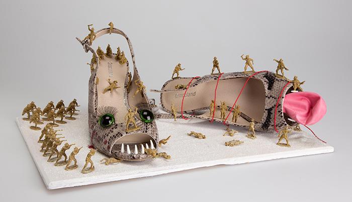 Foto eines Schuhpaares in Form von Pumps mit Reptilmuster mit aufgeklebten großen grünen bewimperten Augen und Zähnen, um und auf denen kleinen Plastikspielfiguren eine Schlacht ausfechten.