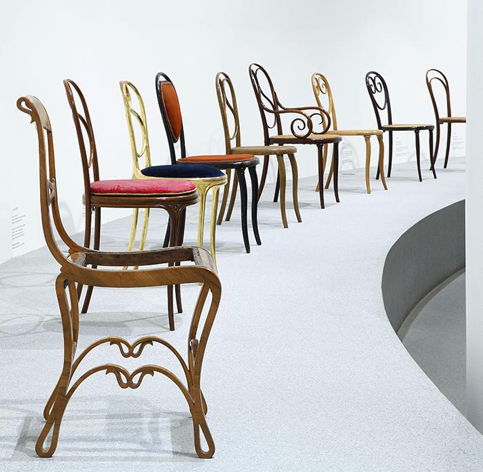 Blick in die Ausstellung auf 9 Stühle mit geschwungenen Holzgestellen