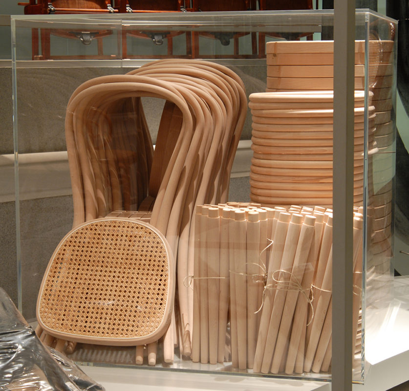 Ein_Kubikmeter-Plexiglaskiste mit Einzelteilen von 36 Holzstühlen