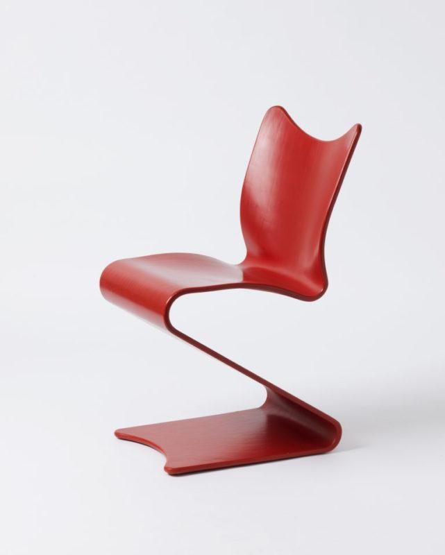 Leuchtend roter Stuhl aus einem langen Holzband geformt als S-Form mit Lehne