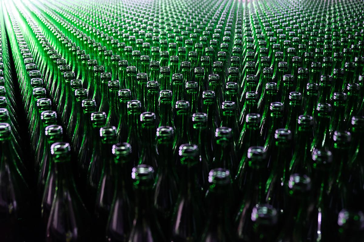 unzählbare grüne Flaschen in Reih und Glied bis zum Bildrand