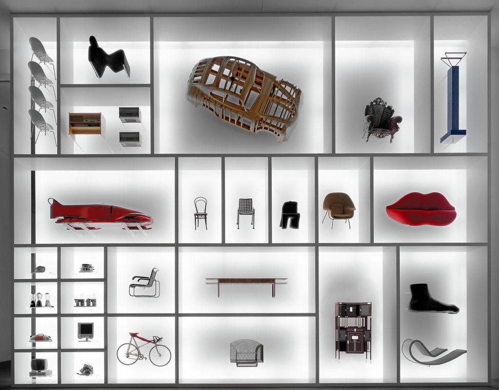 Eine Wand wie ein Setzkasten mit vielen Abteilungen, in denen außergewöhnliche Stühle, Sofas, Tische, Elektrogeräte und Sportgeräte zu sehen sind
