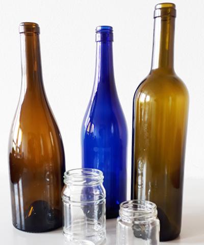 drei verschiedenfarbige große Weinflaschen und zwei leere Marmeladengläser