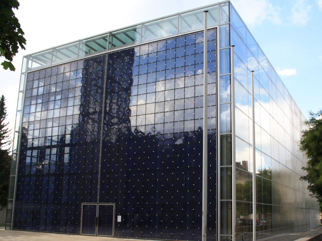 komplett verglaste Fassade einer katholischen Kirche in München mit teils blau gefärbten Scheiben