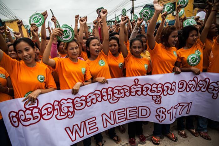 Arbeiterinnen in Uniform demonstrieren mit Banner für mehr Gehalt