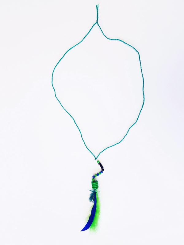 Ein Wollfaden, den man sich um den Hals hängen kann. Daran geknotet: ein Faden, auf den Perlen gefädelt und an dessen Ende Federn befestigt sind
