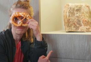 Frau mit Salzbreze neben Salzblock im Museum